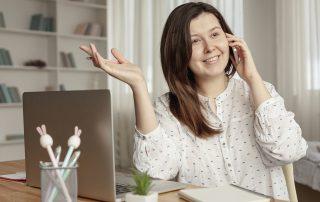 Mujer en casa hablando por teléfono y trabajando con el ordenador
